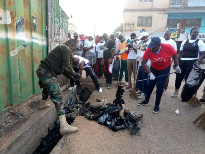 Photo showing Madam Paulina Patience Abayage in red T-shirt collecting rubbers from a gutter