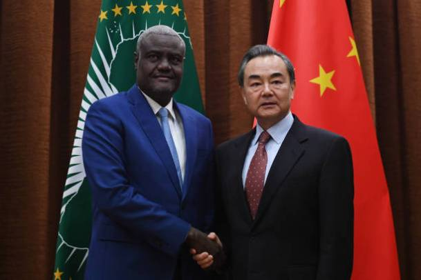 African Union chief Moussa Faki Mahamat (L) shakes hands with China's Foreign Minister Wang Yi before their meeting in Beijing on February 8, 2018.
