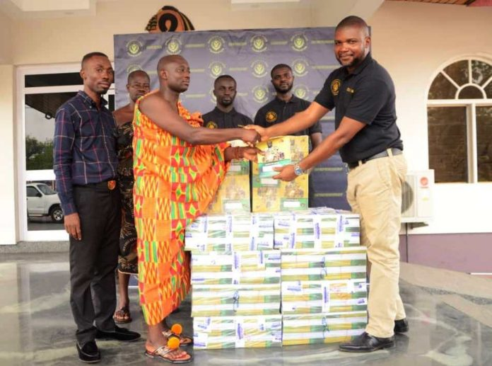 Mr Fred Kyei Sapong (right), the Executive Director of Oheneba Poku Foundation presenting the books to Ankobiahene Baffuor Kwame Kusi (left).