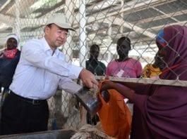 Liu Xianfa (L), then Chinese Ambassador to Kenya, distributes maize donated by Chinese government to refugees at the Kakuma refugee camp in Kenya, June 7, 2017. (Xinhua/Sun Ruibo)