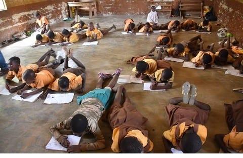 School children lie on floor to write examination