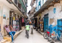 Stone Town, Tanzania - September 9, 2015: View on typical narrow Stone Town street with souvenir shops on Zanzibar island. Man is sitting on a small chair in front of his shop. Bikes and motors are parked on the street.Typical buildings with Arabic and Indian influance.