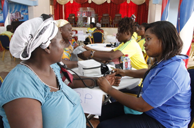 Photo of some health professionals (right) attending to patients (left)
