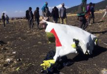 People walk past a part of the wreckage at the scene of the Ethiopian Airlines Flight ET 302 plane crash, near the town of Bishoftu, southeast of Addis Ababa, Ethiopia. Tiksa Negeri, Reuters