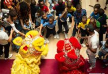 Lion dance performers from the Huaxing Arts Troupe interact with children at the Disbury College in Lagos, Nigeria, March 14, 2019. For more than three months, the Huaxing Arts Troupe, mainly composed of young Nigerian performers, has been going around some local primary and secondary schools in Lagos, promoting the Chinese and Nigerian cultures through music and dance. (Xinhua/Lyu Shuai)