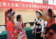 Fan Yongzhen (2nd R), a deputy to the 13th National People's Congress (NPC), talks with her fellow deputies after a plenary meeting of Yunnan delegation in Beijing, capital of China, March 7, 2019. (Xinhua/Yang Zongyou)