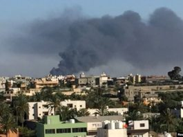 FILE - Smoke rises during a fight between members of the Libyan internationally recognized government forces and Eastern forces in Ain Zara, Tripoli, Libya, May 5, 2019.