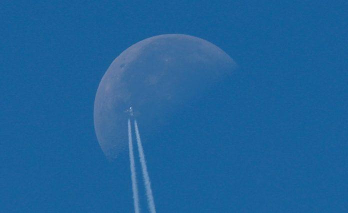 A passenger plane flies in the sky as the Moon is seen in Berlin, Germany, August 23, 2019. REUTERS/Fabrizio Bensch