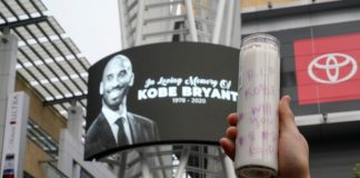 A mourner holds up a lit candle in Microsoft Square near the Staples Center to pay respects to Kobe Bryant after a helicopter crash killed the retired basketball star, in Los Angeles, California, U.S., January 26, 2020. REUTERS/Kyle Grillot