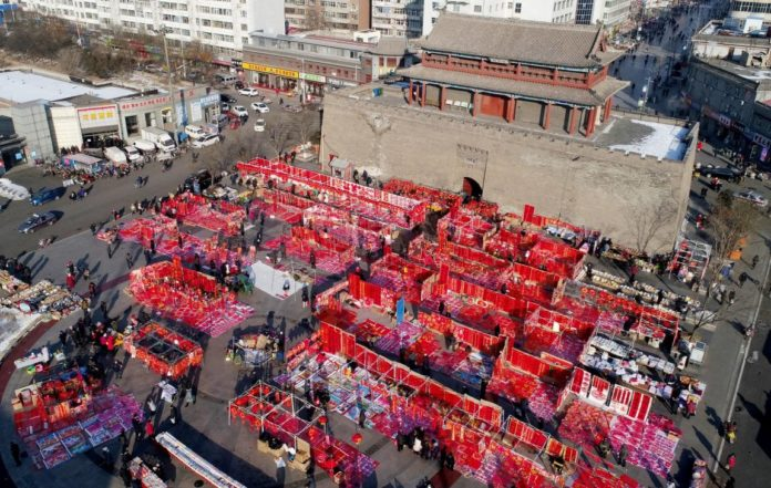 People buy Spring Festival couplets and decorations at a Spring Festival fair in front of the south gate of the ancient Xuanhua city in Zhangjiakou city, north China's Hebei Province, Jan.14, 2020. (Photo by Chen Xiaodong/People's Daily Online)