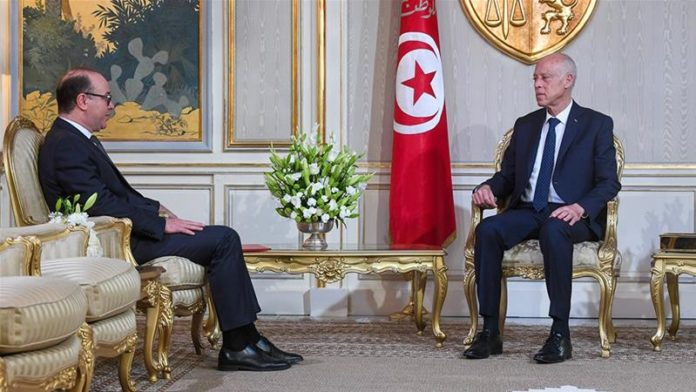 Elyes Fakhfakh, left, served as finance and tourism minister following the 2011 uprising [Tunisian Presidency/Anadolu]