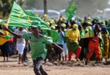 A boy runs with a flag during a ruling Chama Cha Mapinduzi (CCM) rally in Dar es Salaam, Tanzania, on October 21, 2015. CCM's party's candidate John Magufuli hopes to succeed President Jakaya Kikwete in what is seen as the tightest electoral race in Tanzania's history, as the main opposition parties unite around ex-prime minister Edward Lowassa, 61, who recently defected from the CCM. AFP PHOTO / DANIEL HAYDUK (Photo credit should read Daniel Hayduk/AFP/Getty Images)
