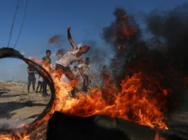 A Palestinian protester uses a slingshot to hurl stones at Israeli troops during clashes with Israeli troops on the Gaza-Israel border, east of southern Gaza Strip city of Khan Younis, Aug. 30, 2019. At least 54 Palestinians were injured on Friday, during clashes with Israeli soldiers in eastern Gaza Strip, close to the border with Israel, medics said. (Xinhua/Stringer)