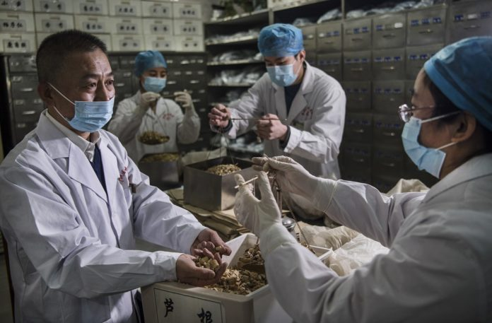Medical staff work at a traditional Chinese medicine pharmacy in Weinan City, northwest China's Shaanxi Province, Feb. 20, 2020. (Xinhua/Tao Ming)