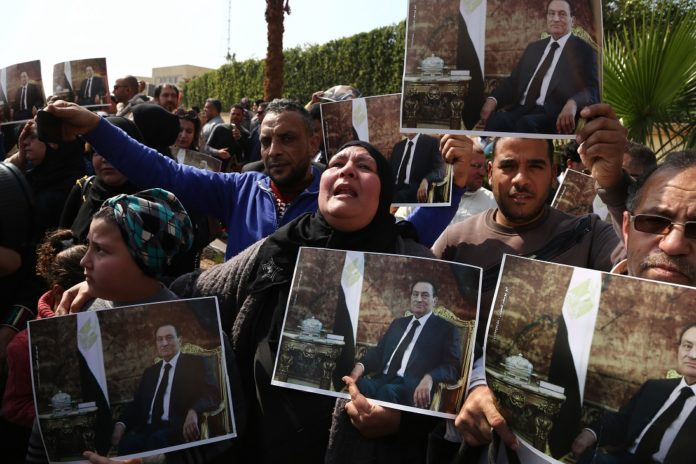 Supporters of former Egyptian President Hosni Mubarak hold pictures of him in Cairo, Egypt, Feb. 26, 2020. Egypt held a military funeral on Wednesday for the country's former president Hosni Mubarak who died on Tuesday at the age of 91. (Xinhua/Ahmed Gomaa)