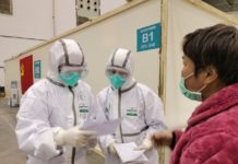 """Medical staff record information of a patient at """"fangcang"""" hospital in a cultural building complex dubbed """"Wuhan Livingroom"""", Feb. 9. (Photo by Li Han, People's Daily)"""