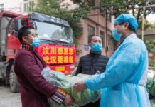 Zhao Yong, Party chief of Longzhu village, Wenchuan county of Sichuan province and his fellow villagers deliver vegetables to a medical staff in Wuhan, Feb. 5. The man, together with 12 of his fellow villagers, have donated vegetables to 12 major hospitals in the city. (Photo by Zhang Wujun/People's Daily)