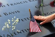A woman touches a plate on which names of 9/11 victims were inscribed at the National September 11 Memorial and Museum in New York, the United States, Sept. 11, 2019. People paid their tributes on Wednesday to mourn the victims of the 9/11 terrorist attacks which happened 18 years ago and claimed thousands of lives. (Xinhua/Li Rui)