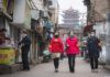 Community workers and volunteers use a speaker to publicize the information about prevention and control of the novel coronavirus at a street near the Yellow Crane Pavilion in Wuhan, central China's Hubei Province, Feb. 7, 2020. (Xinhua/Xiao Yijiu)