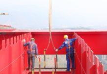 Construction workers help hoist a girder on the 230-meter-high Yuanjiang Railway Bridge along the Yuxi-Mohan section of China-Laos Railway. Photo by Ye Chuanzeng, Li Hong, People's Daily
