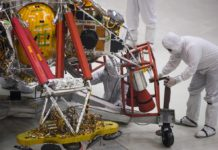 """NASA engineers and technicians reposition the Mars 2020 spacecraft descent stage December 27, 2019 during a media tour of the spacecraft assembly area clean room at NASA's Jet Propulsion Laboratory in Pasadena, California. - The Mars 2020 rover, which will take off in a few months to the Red Planet, will not only search for possible traces of past life, it will also serve as a """"precursor to a human mission to Mars,"""" NASA scientists said December 27, 2019, when presenting the spacecraft to the press. The Martian robot made its first turns of wheel last week in the large sterile room of the Jet Propulsion Laboratory (JPL) in Pasadena, near Los Angeles, where it was born. It is scheduled to leave Earth in July 2020 from Cape Canaveral (Florida) and land on Mars in February 2021. (Photo by Robyn Beck / AFP)"""