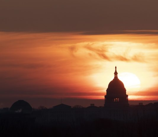 The U.S. Capitol Building is silhouetted against sunrise in Washington D.C., the United States, on March 18, 2020. U.S. President Donald Trump said on Wednesday he will invoke the Defense Production Act, which allows the administration to force American industry to ramp up production of medical supplies, to combat the COVID-19 pandemic. (Xinhua/Liu Jie)