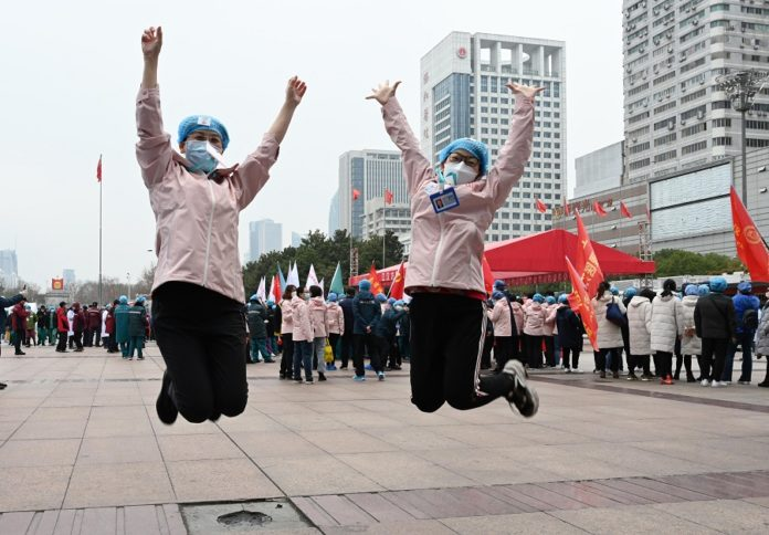 The largest Fang Cang makeshift hospital in the epicenter Wuhan, in Central China's Hubei Province, purposely built and designed for COVID-19 treatment, closed on Monday. The two doctors are happy celebrating for it. Photo by Jin liusi/People's Daily online