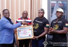 Picture shows the Ghana Boxing Federation president, Mr. George Lamptey and the Black Bombers presenting a certificate of appreciation to the GOC