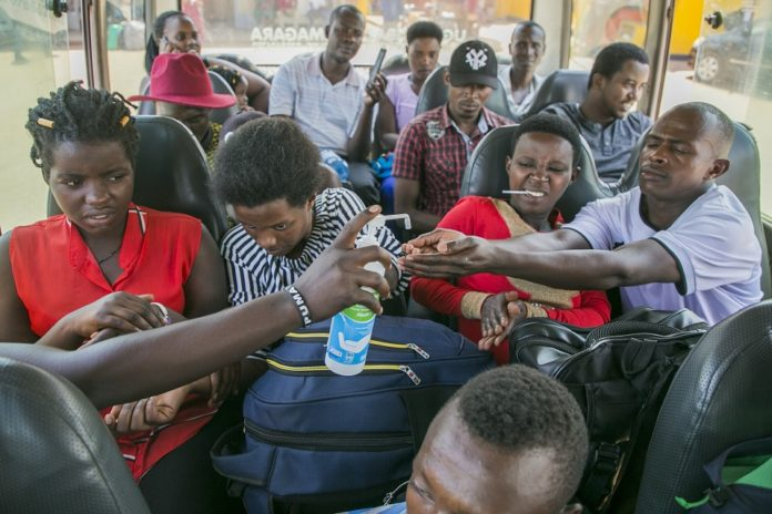 Bus passengers sanitize their hands in Kigali, capital city of Rwanda, March 14, 2020. Rwanda on Saturday registered its first case of the novel coronavirus (COVID-19), the ministry of health said here. (Xinhua/Cyril Ndegeya)