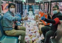 Community workers and volunteers from Tangcai community, Jianghan district, Wuhan loaded a bus with 11-product packages, Feb. 24, 2020. In order to win the battle against the epidemic, all communities in Wuhan are under closed-off management. Li Changlin/ People's Daily Online