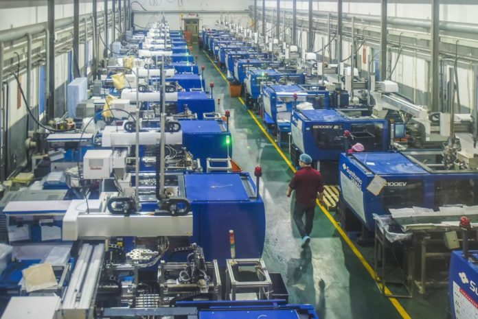 Workers check machines at a workshop of Ningbo Jieli Cosmetical Package company in Yuyao, east China's Zhejiang Province, Feb.25, 2020. Enterprises in the city have smoothly restarted production, making the most of intelligent equipment such as automated production lines and intelligent robots. Photo by Zhang Hui, People's Daily Online