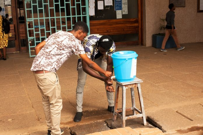 Students wash their hands before entering the library in Blantyre, Malawi, March 23, 2020. Malawi President Peter Mutharika has declared a state of national disaster in Malawi over COVID-19 and he has since ordered closure of all public and private schools, colleges and universities effective Monday. (Xinhua/Joseph Mizere)