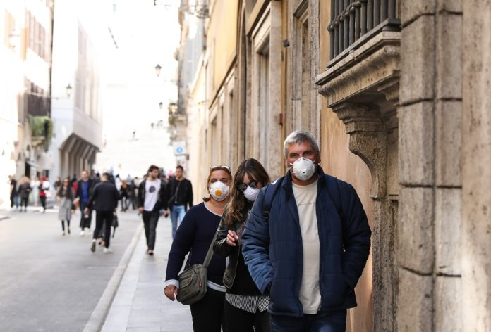 Pedestrians wearing face masks walk on a street in Rome, Italy, March 10, 2020. Italian Prime Minister Giuseppe Conte announced late Monday that the whole of Italy will be placed under lockdown from Tuesday until April 3. (Xinhua/Cheng Tingting)