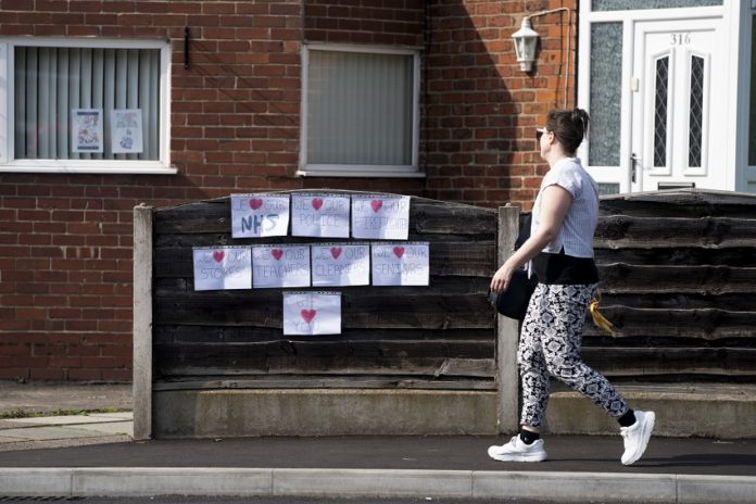 A woman walks past signs in support of the NHS (National Health Service) and others during the COVID-19 outbreak in Manchester, Britain, on April 10, 2020. The death toll of those hospitalized in Britain who tested positive for the COVID-19 reached 8,958 in Britain, marking a record-high daily increase of 980, Health Secretary Matt Hancock said Friday. As of Friday morning, a total of 73,758 cases of COVID-19 have been confirmed in Britain, according to the Department of Health and Social Care. (Photo by Jon Super/Xinhua)