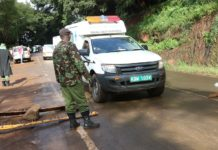 An ambulance carrying a patient passes through a police roadblock at Chania River in Thika, Kiambu County, Kenya, Kenyan President Uhuru Kenyatta has banned all movement by road, rail or air in and out of the Nairobi metropolitan area with effect from 7 p.m. on Monday. (Xinhua/Allan Mutiso)