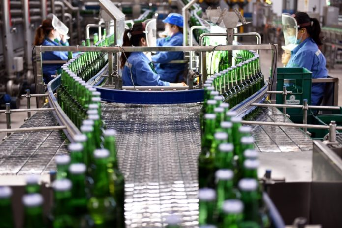 Employees work on a production line in Tsingtao Brewery (Zhangjiakou) Co., Ltd. in Xuanhua economic development zone, north China's Hebei province, April 18, 2020. Photo by Chen Xiaodong, People's Daily Online