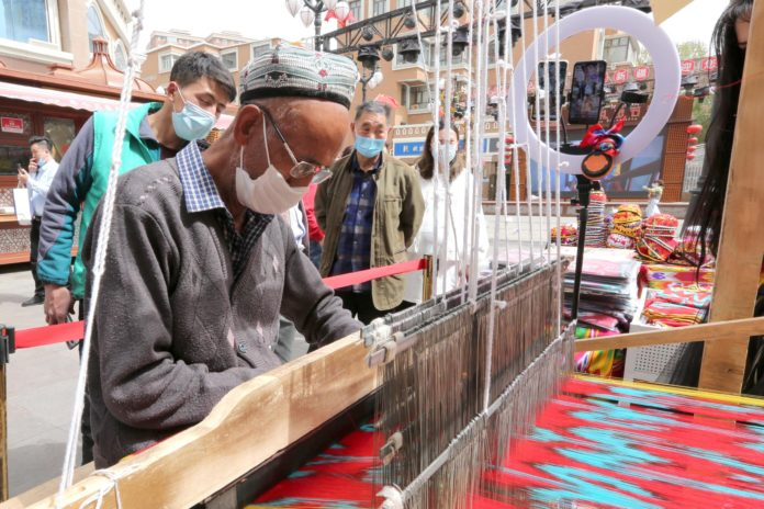 Uygur senior Amal Ali livestreams the making of Etles Silk, a type of Ikat that Uyghurs used traditionally for woman's clothing, at the Xinjiang International Grand Bazaar, April 14. Photo by Cai Zengle, People's Daily Online