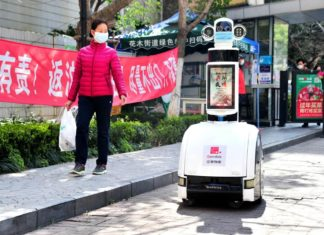 A robot is broadcasting epidemic prevention knowledge in Shanghai, with four cameras on top of it recording the environment, Feb. 27, 2020. Photo by Yang Jianzheng, People's Daily Online