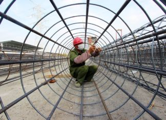 A worker stabilizes a cylinder-shaped steel tube for bridge pier construction at a bridge construction site in Taizhou city, east China's Zhejiang province, March 19, 2020. Jiang Youqing, People's Daily Online