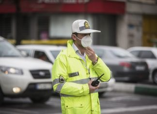 An Iranian policeman adjusts his mask on a street in Tehran, Iran, on March 7, 2020. The novel coronavirus has claimed 194 lives in Iran, the Ministry of Health and Medical Education announced Sunday. Kianush Jahanpur, head of Public Relations and Information Center of the ministry, said the total number of the confirmed cases now stands at 6,566, of whom 2,134 have recovered. Tehran records 1,805 cases of infection, the highest number among the country's provinces, followed by Qom with 685 cases and Mazandaran with 620 cases. (Photo by Ahmad Halabisaz/Xinhua)