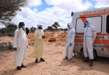 Family members of a person that died of COVID-19 converse with health workers during a burial ceremony, on the outskirts of Mogadishu, Somalia, May 8, 2020. Somali health ministry on Sunday confirmed 57 new cases of the novel coronavirus, bringing the total infections to 1,054. Fawziya Abikar, health minister said three people succumbed to the deadly respiratory disease, raising the death toll to 51. (Xinhua/Hassan Bashi)