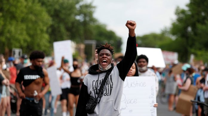 Protesters gather at the scene where George Floyd, an unarmed Black man, was pinned down by a police officer kneeling on his neck before later dying in hospital in Minneapolis, Minnesota, the US [Eric Miller/Reuters]