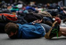 Protesters lie down for a minute of silence in the position George Floyd was in when he died during a rally against police brutality and the death in Minneapolis police custody of George Floyd, in Seattle, Washington, U.S. June 2, 2020. REUTERS/Lindsey Wasson