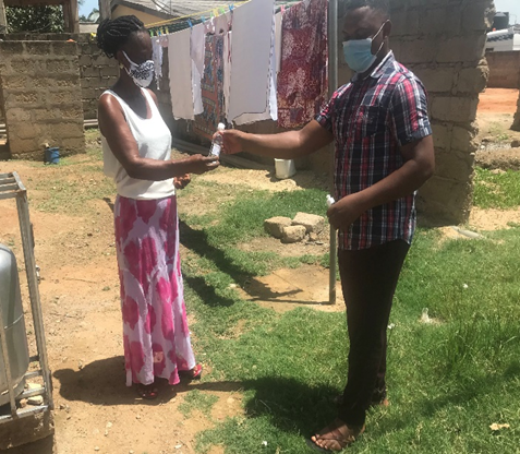 Presentation and use of hand sanitizer to a lady at Adidome, Central Tongu District