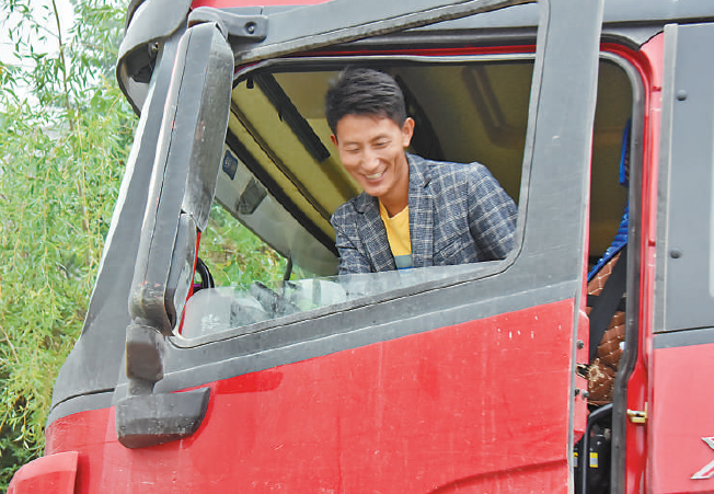Photo shows Lu Qula and his new truck. (Photo by Qiu Xingchun/People's Daily Online)