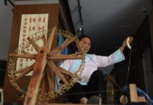 Photo shows a senior woman of the Buyi ethnic group makes yarn with a spinning wheel. Photo by Zhang Chunlei
