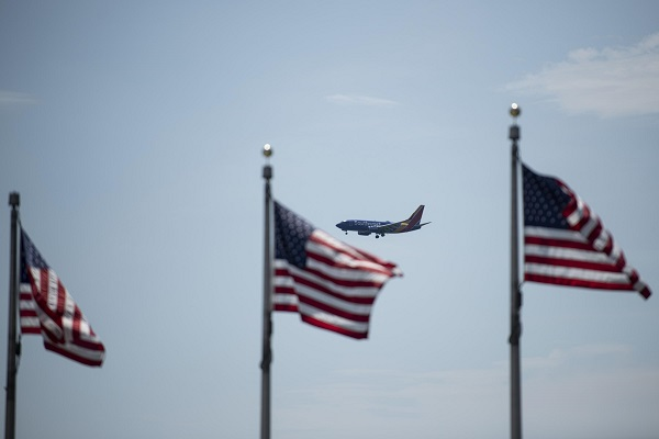 A plane flies in the sky with the U.S. national flags in the foreground in Washington, D.C., the United States, on July 21, 2020. U.S. President Donald Trump said Tuesday afternoon that the coronavirus pandemic in the United States will probably