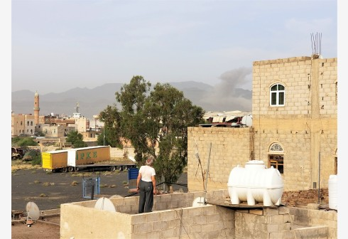 SANAA, June 16, 2020 (Xinhua) -- A resident looks at rising smokes after an airstrike in Sanaa, Yemen, June 16, 2020. The Saudi-led coalition in Yemen launched on Tuesday morning at least five airstrikes on the capital Sanaa held by the Houthi rebels, the Houthi-run al-Masirah TV reported. The airstrikes hit Houthi-controlled military sites on the hills of al-Subahah, Attan and Nahdain in and around the center of the Yemeni capital city, local residents said. (Photo by Mohamed al-Azaki/Xinhua)