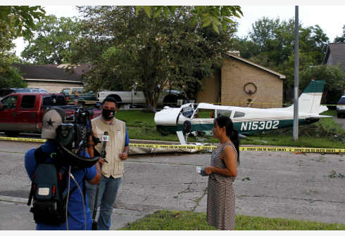 HOUSTON (U.S.), July 28, 2020 (Xinhua) -- Reporters work at the scene of a plane crash in Houston area of Texas, the United States, on July 28, 2020. Two people were injured when the small plane crashed on Tuesday morning into a neighborhood in Houston area. (Photo by Steven Song/Xinhua)