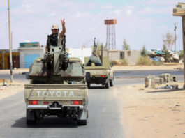 A fighter of the UN-recognized Libyan government gestures on a pickup truck in the Abu Qurain area about 300 kilometers east of the Libyan capital Tripoli, July 20, 2020.